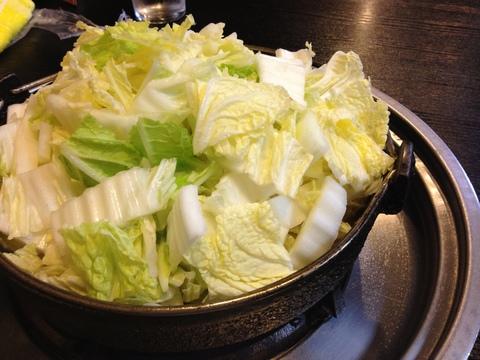 浅い鉄鍋には水はなく肉と山盛りの白菜のみ
