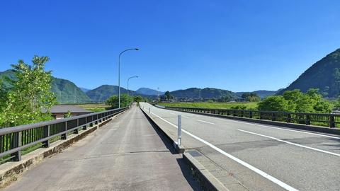 大日川にかかる大日橋(平成15年10月架)]。奥には先程の巨大な加賀幹線が雲龍山から降りてきている