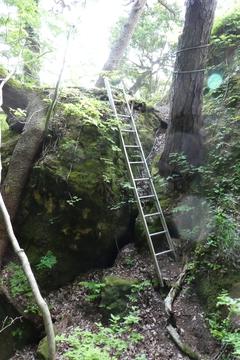 洞窟の前にハシゴがかけられた展望岩へ
